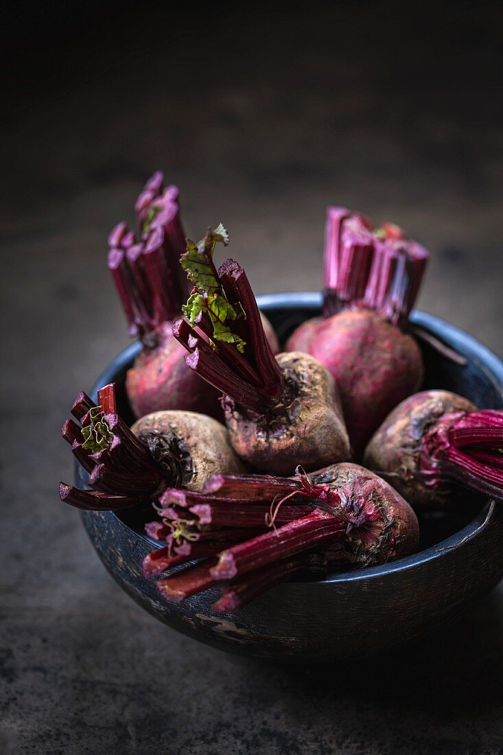 A bunch of red beets with their leaves cut off in a dark wood bowl