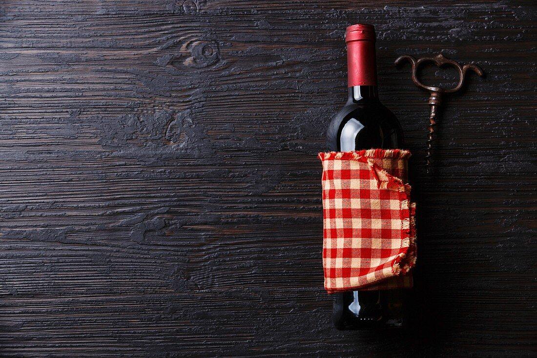 Wine bottle and corkscrew on Black Burned wooden background