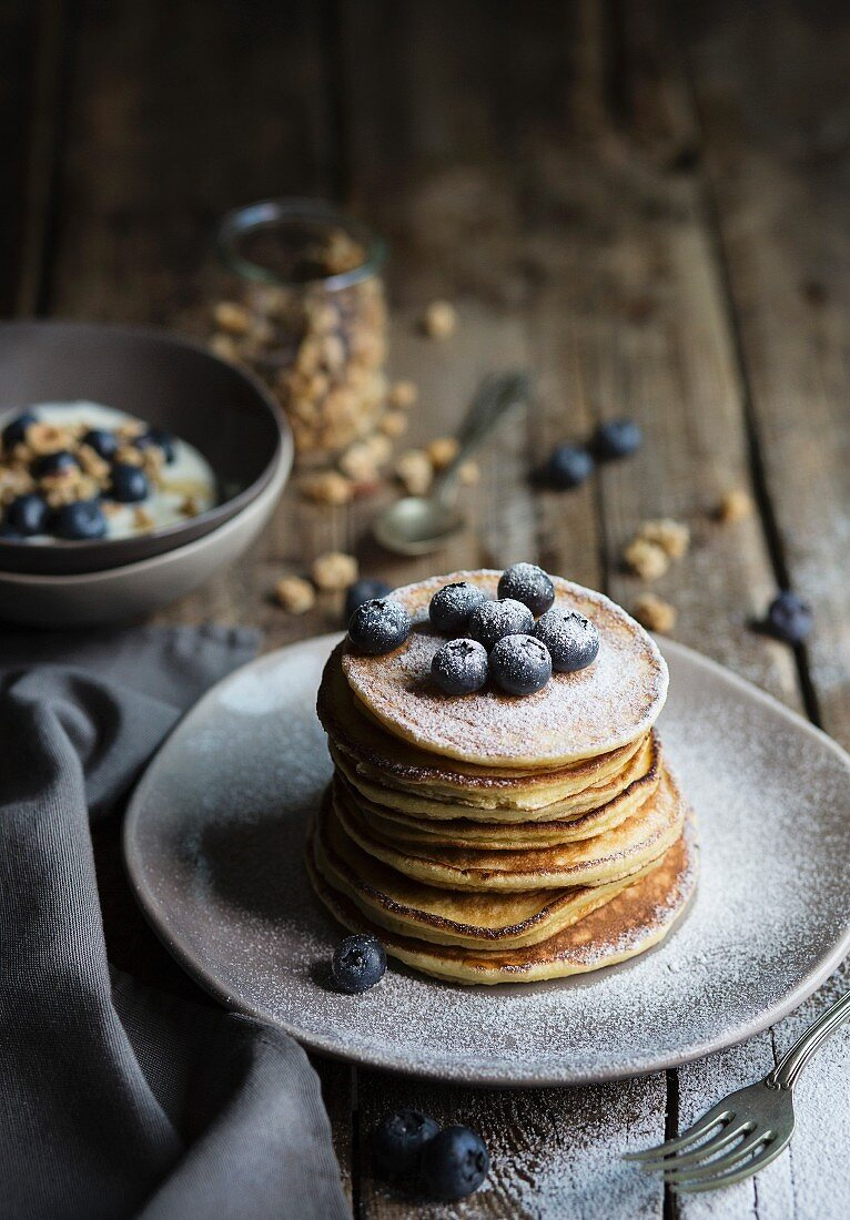Breakfast table with pancakes served with blueberries and icing sugar and yogurt with muesli