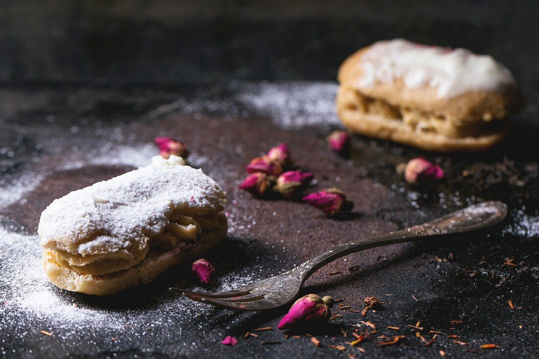 Eclairs with sugar powder, served with dry tea rose buds and vintage cutlery over dark background