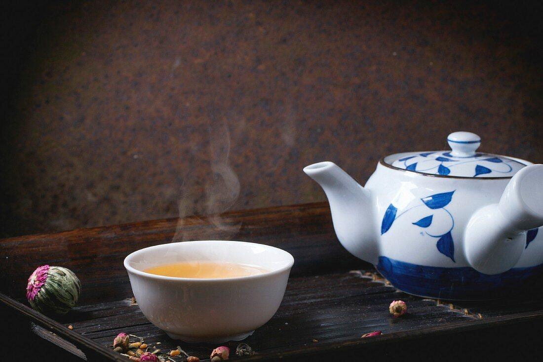 Teekanne und Teeschale mit grünem Tee serviert auf Bambus-Tablett (Japan)