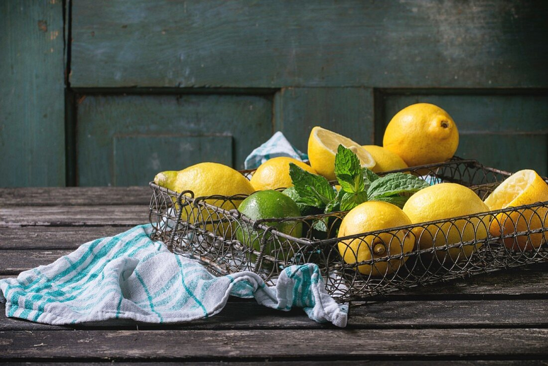 Heap of whole and sliced lemons and limes with mint in vintage metal grid box over old wooden table