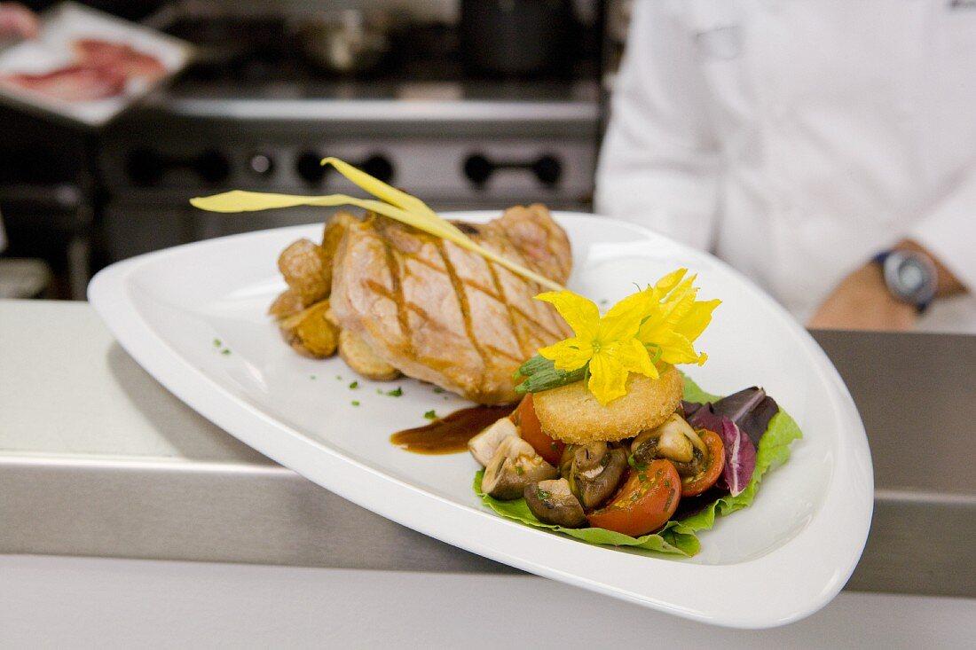 Grilled pork chop with vegetables at a restaurant pick up station