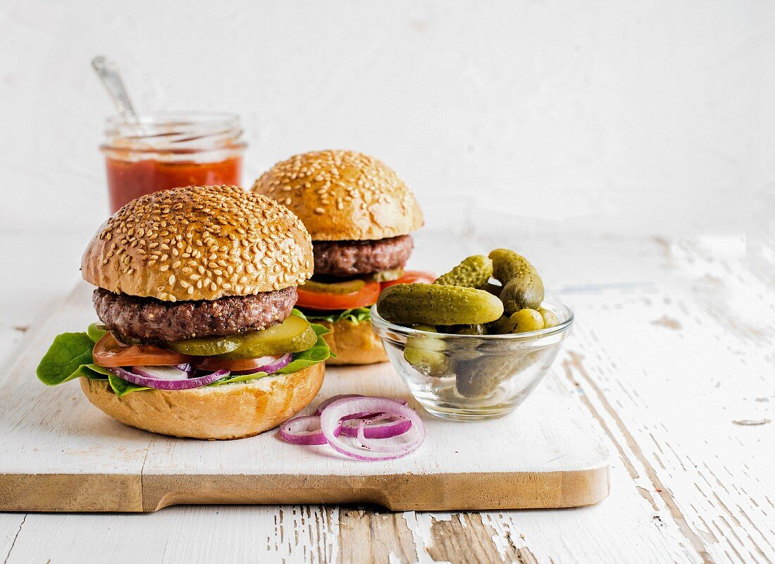 Two fresh homemade burgers served with pickles and onion rings on wooden serving board over white background