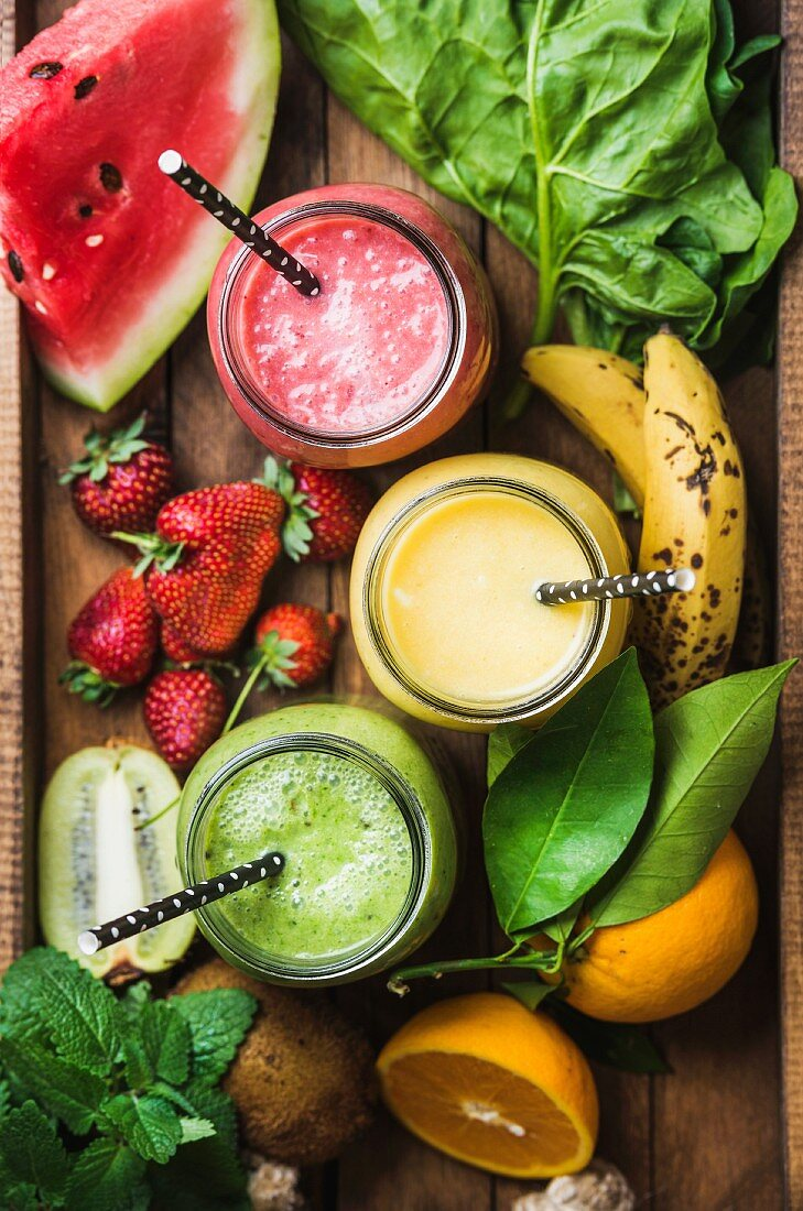 Fresh blended smoothies in glass jars with straws