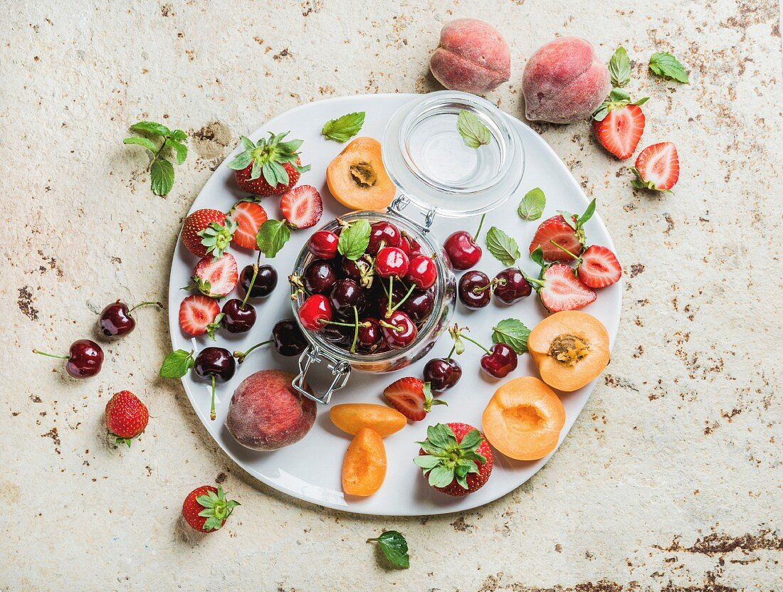 Healthy summer friut variety. Sweet cherries in glass jar, peaches, strawberries, mint leaves on white serving plate