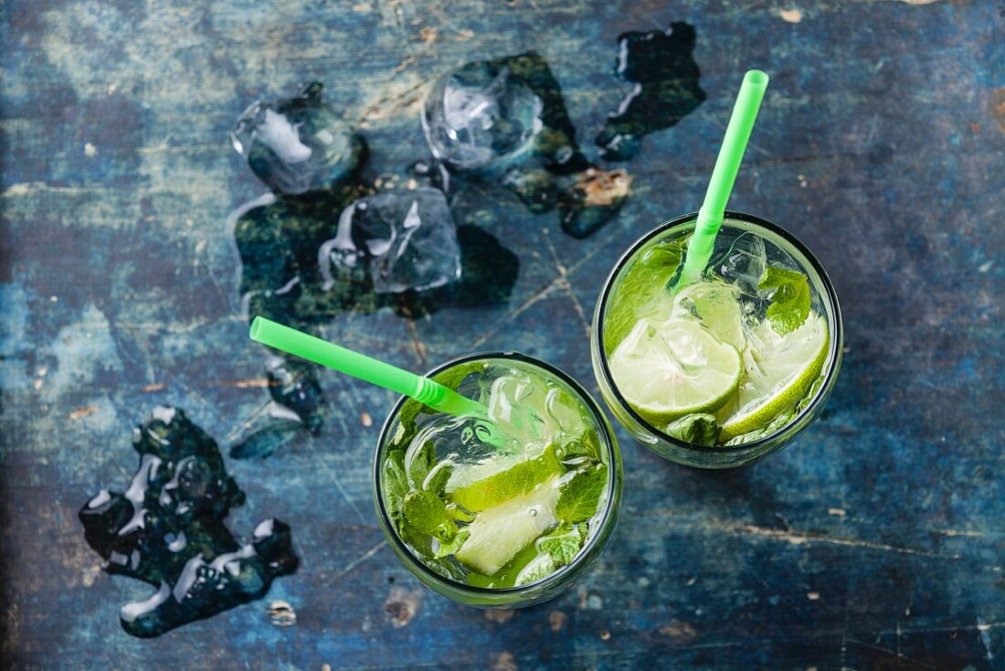 Glass of iced Mojito cocktail with mint on blue background