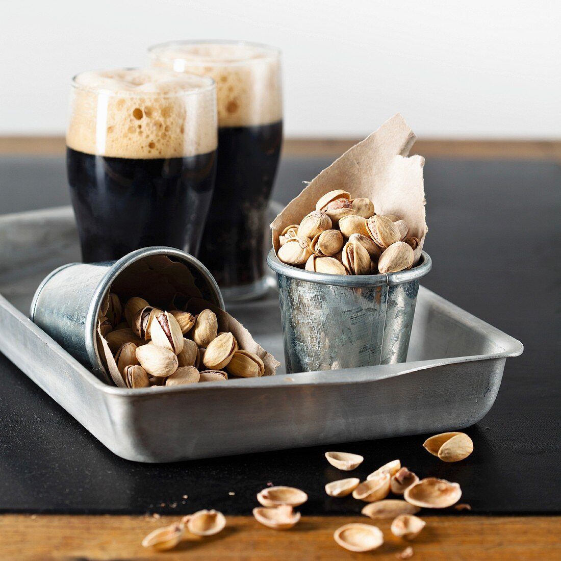 Dark beer and pistachios at textured table