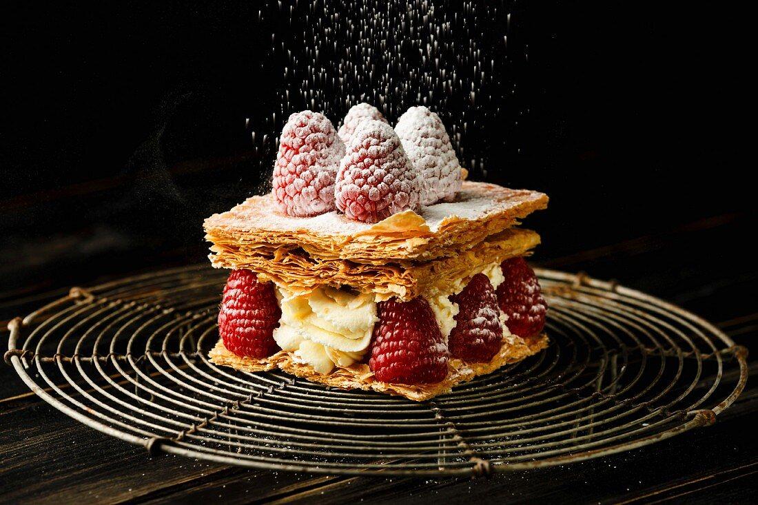 Millefeuille dessert with raspberry on black background