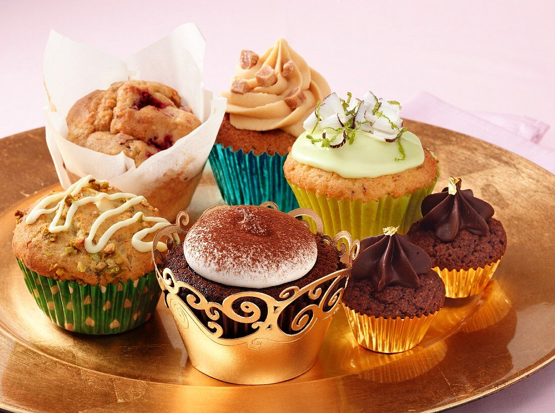 A selection of different luxury cupcakes on a gold plate sitting on a pink background