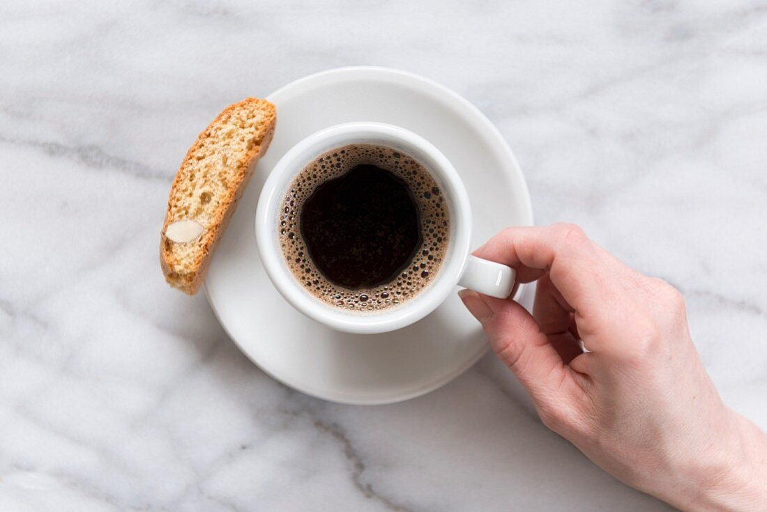 Black coffee on a marble worktop, with biscotti biscuit