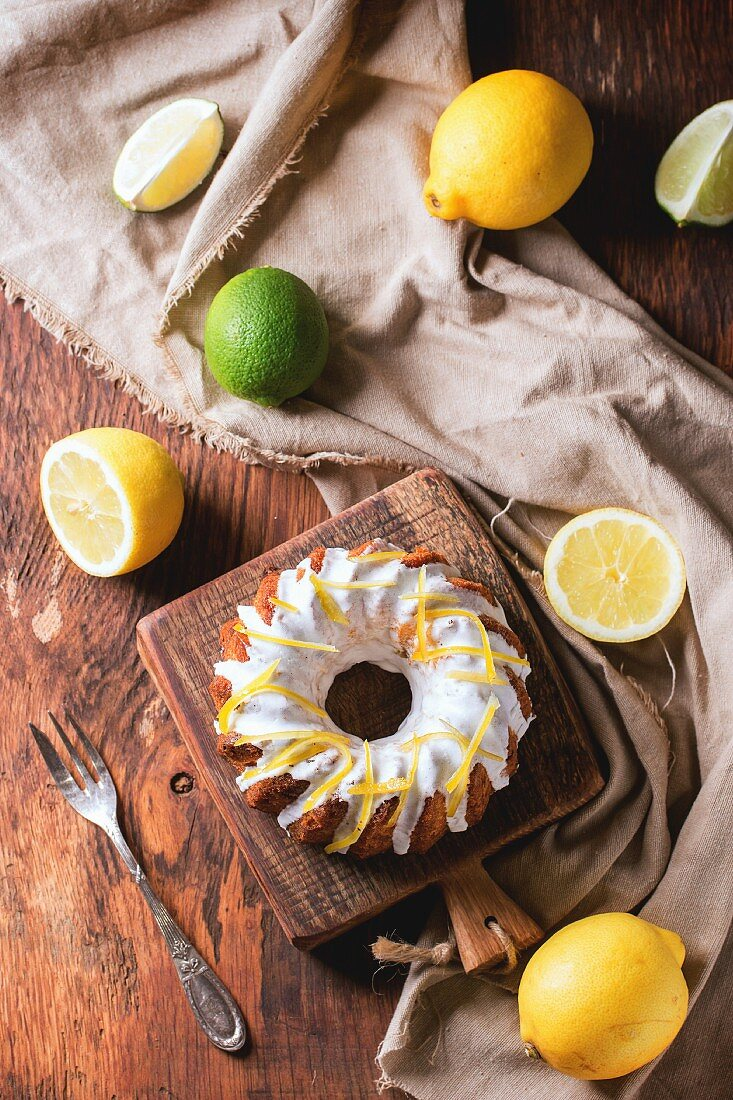 Homemade cakes with white frosting and lemon zest, served with lemons and lime