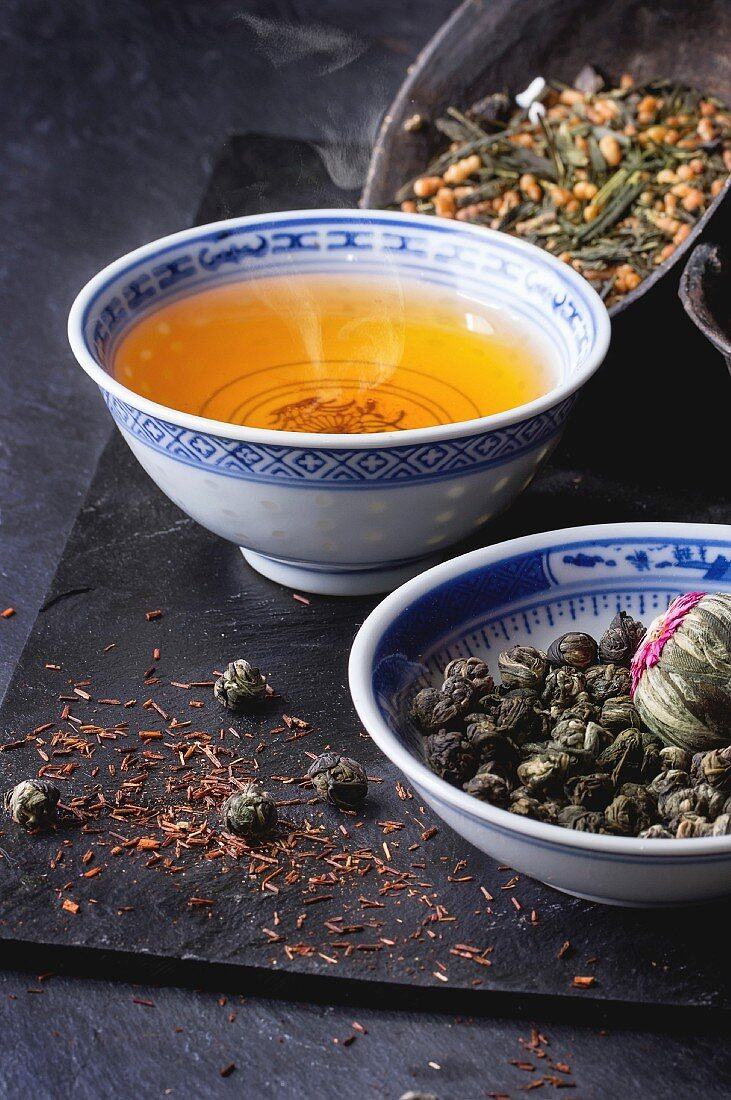 Assortment of dry tea and cup of hot tea: Green tea, black tea, green tea with rice, rooibos, dry rose buds