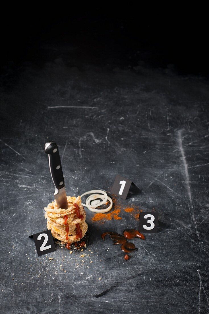 Onion rings, a knife, and ketchup arranged in the style of a crime scene