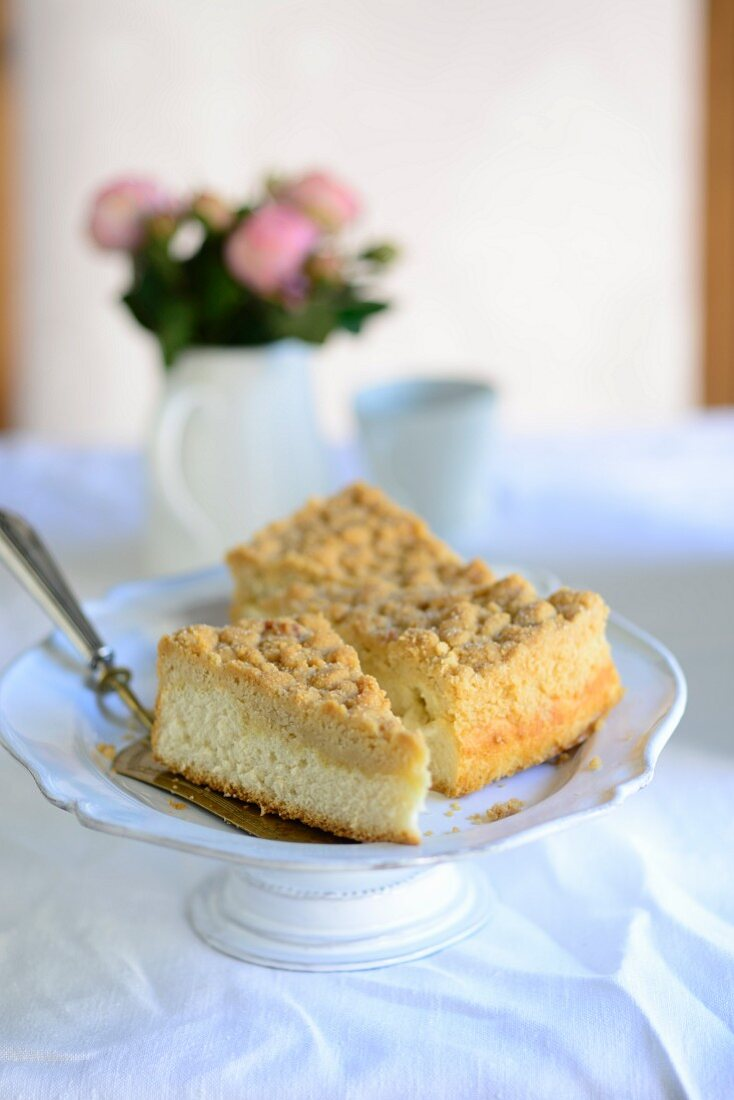Three pieces of streusel cake on a cake stand