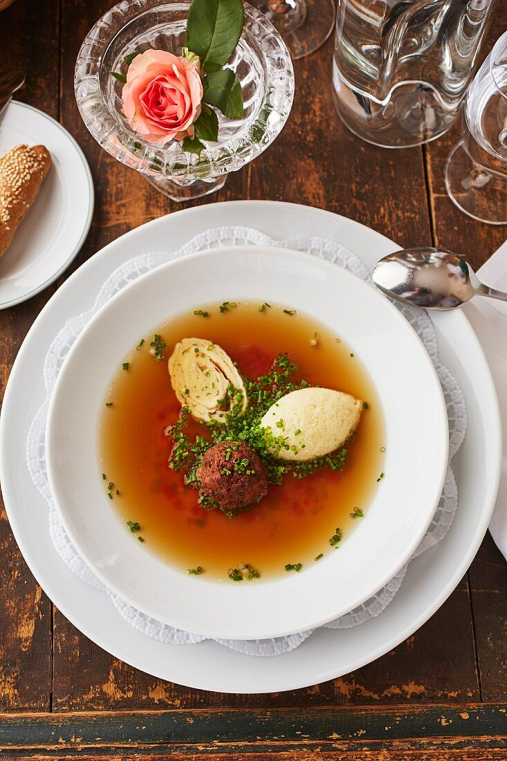 Beef broth with three different toppings: liver dumpling, semolina dumpling and a shredded pancake