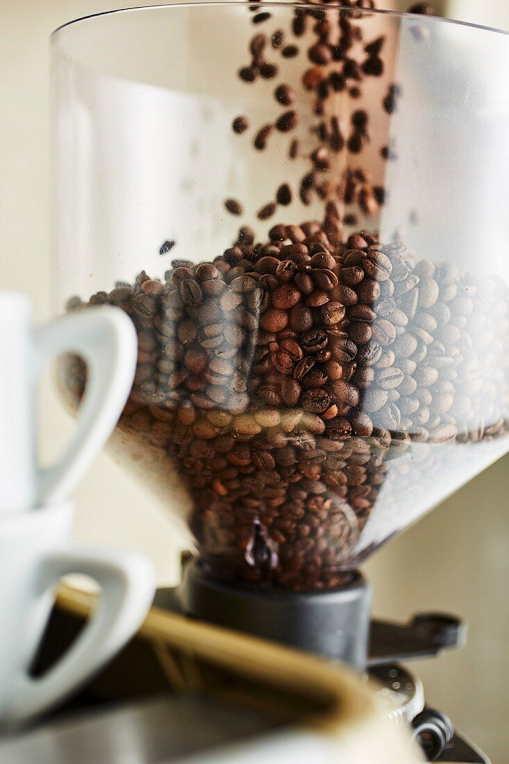 Coffee beans falling into a coffee mill