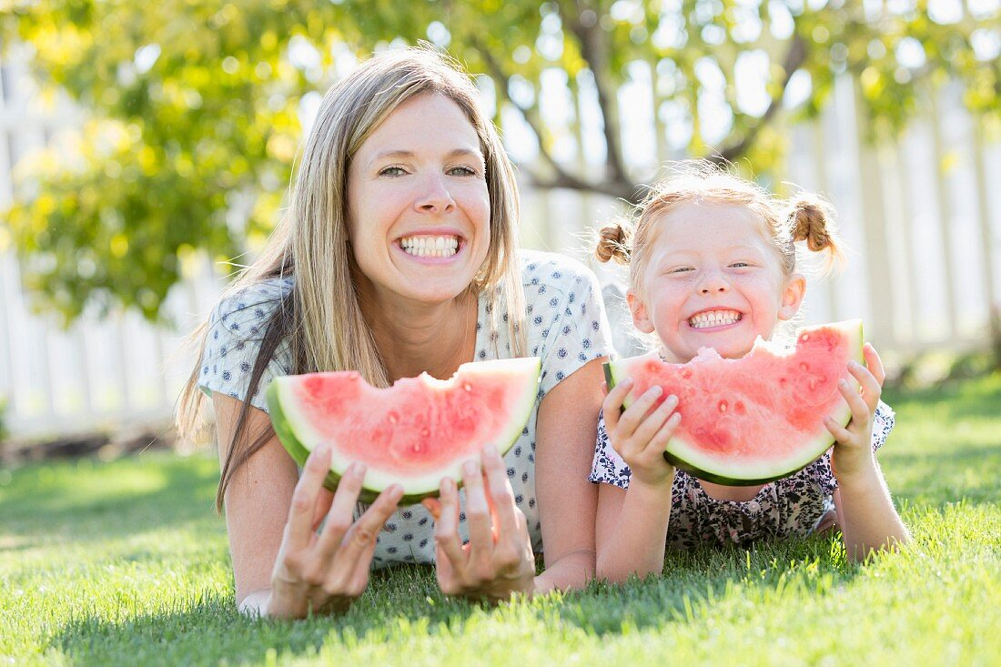A mother and daughter lying on the grass eating watermelon