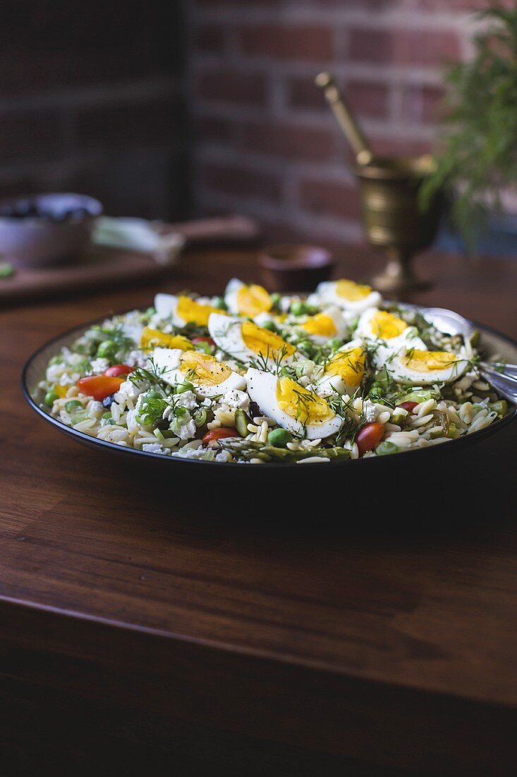 A large bowl of Mediterranean-Style Orzo Salad with Spring Vegetables