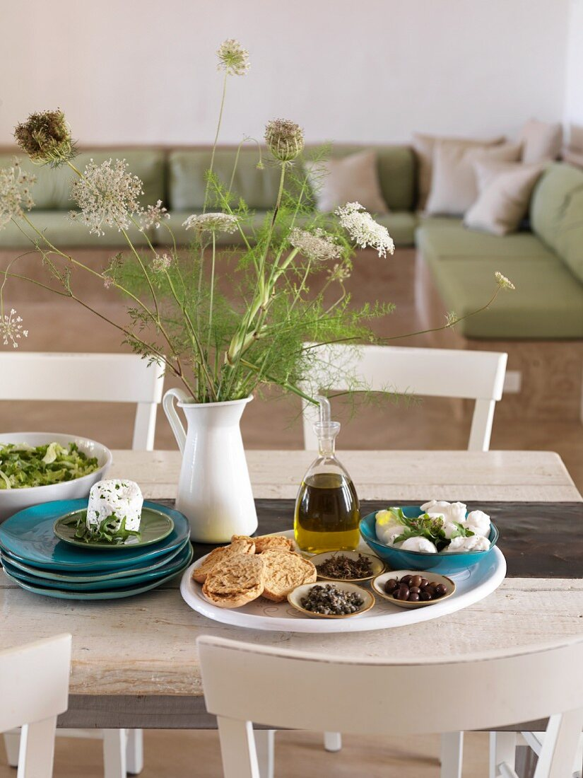 Table set with olive oil, cheese and bread in living area