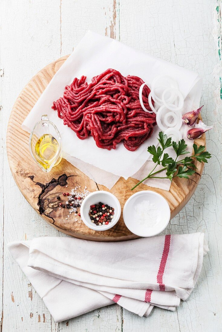 Fresh minced meat with onion and spices on wooden cutting board on blue background