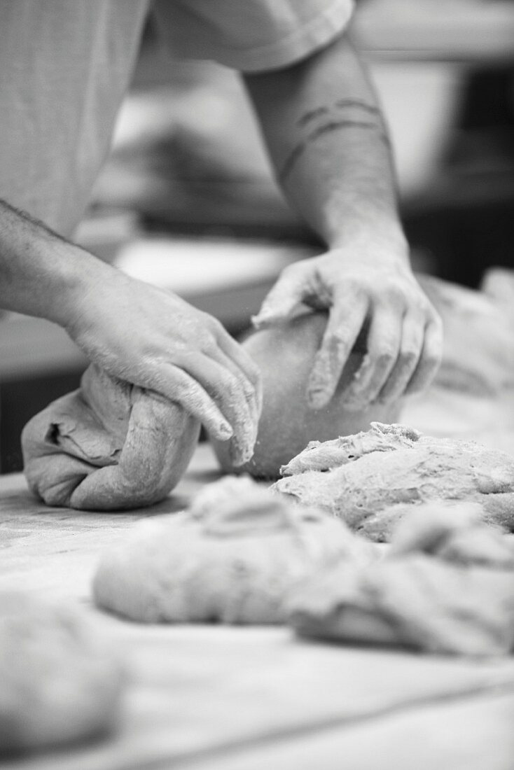 A baker kneading dough in his bakery