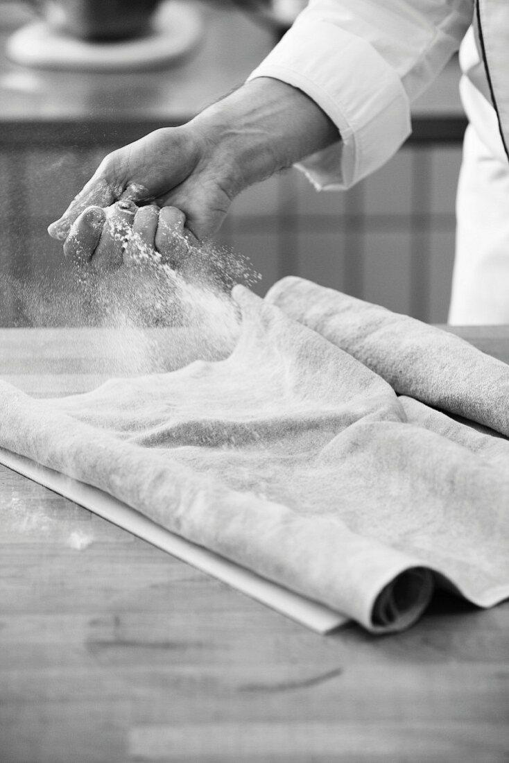 A baker dusting flour