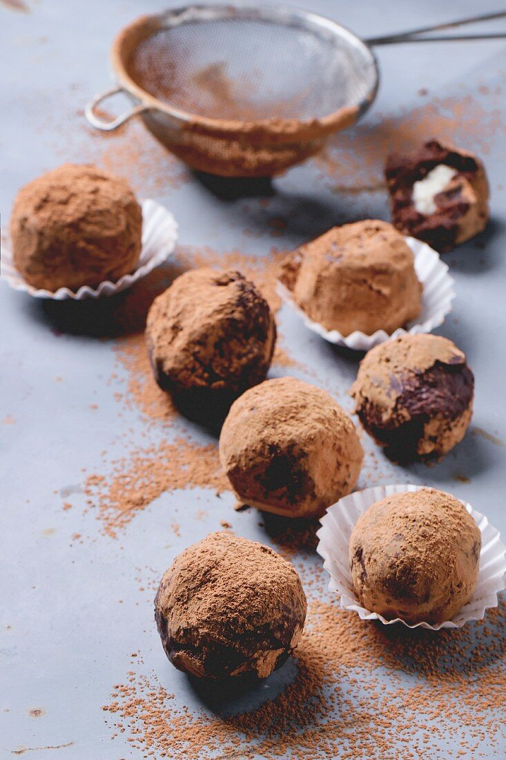 Homemade chocolate truffles with marzipan and cocoa powder over gray matal surface