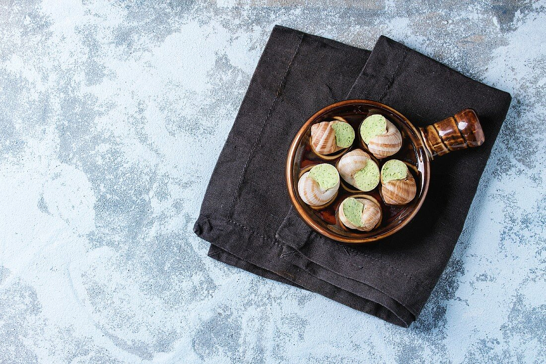 Uncooked Escargots de Bourgogne - Snails with herbs butter, gourmet dish, in traditional ceramic pan