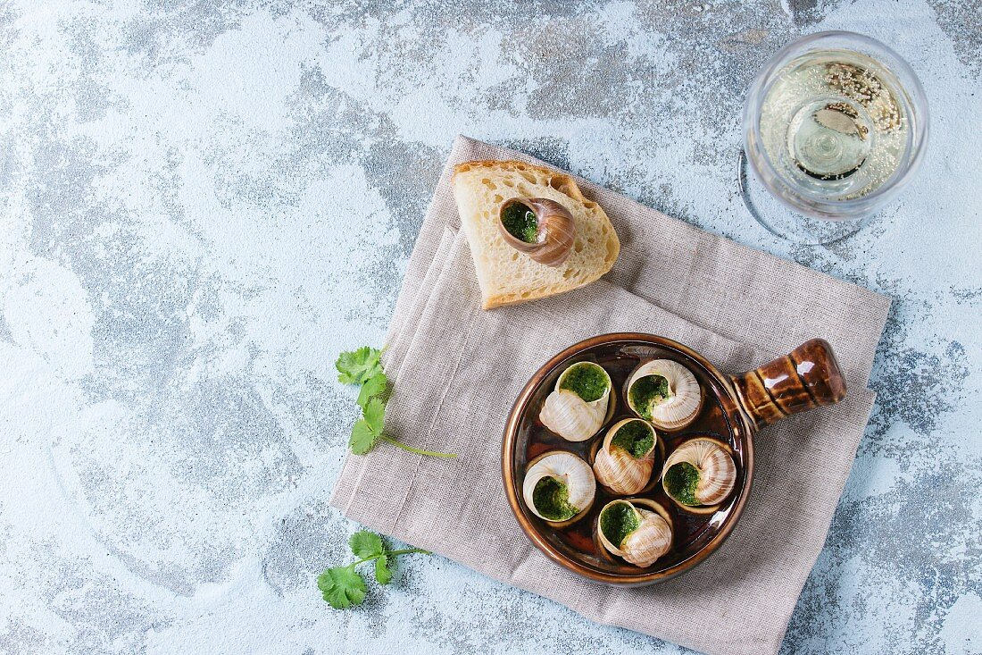 Escargots de Bourgogne - Snails with herbs butter with parsley, bread and glass of white wine