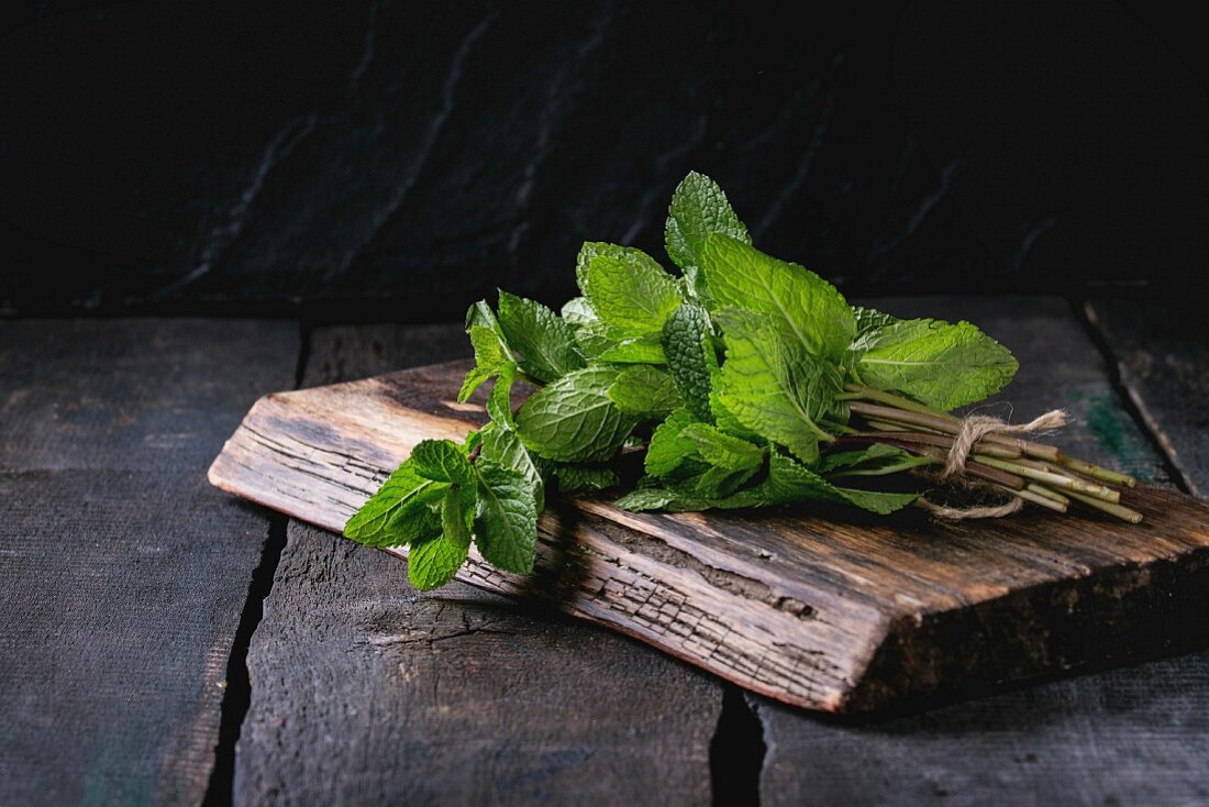 Bunch of fresh mint with thread on wooden chopping board over old wooden background