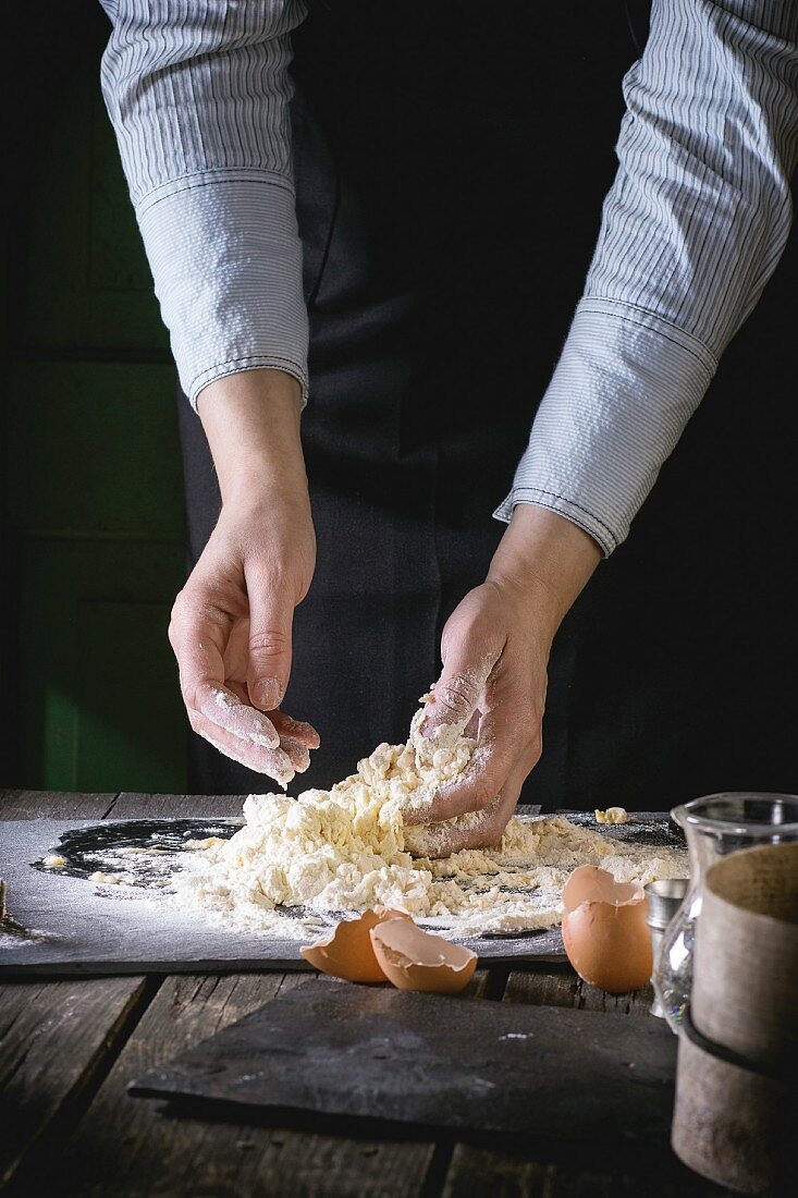 Female hands knead the dough for pasta on old wooden kitchen table, broken eggs at foreground