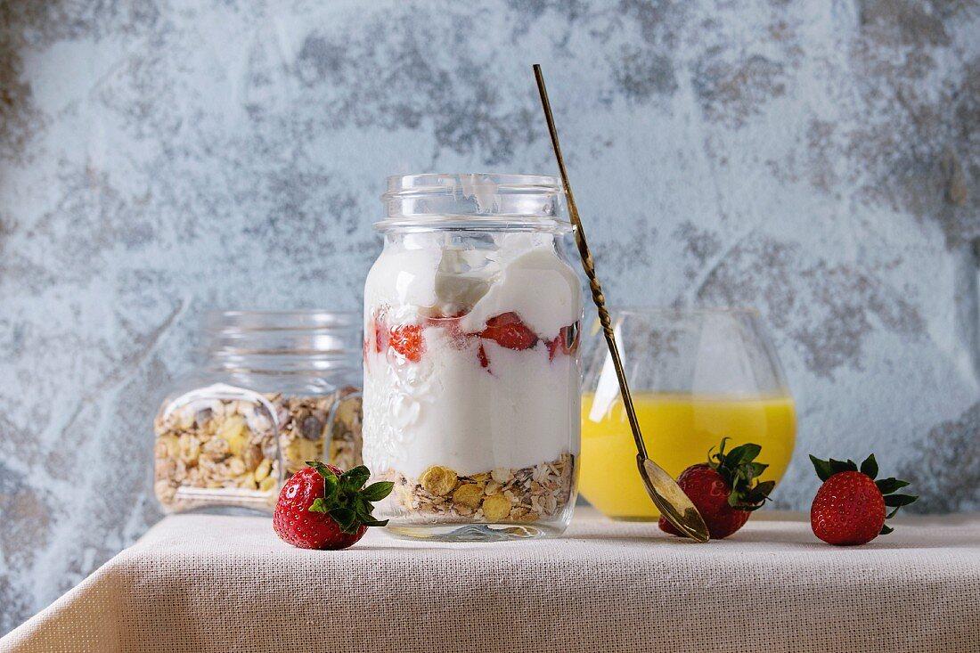 Muesli, strawberries and yogurt with mango smoothie in glass mason jars, served with fresh strawberry