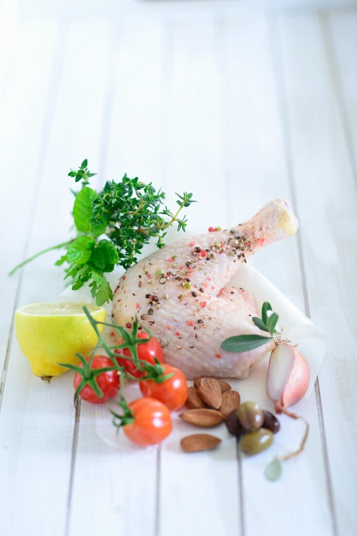 A spiced chicken leg with onion, olives, almonds, cherry tomatoes, lemon and herbs