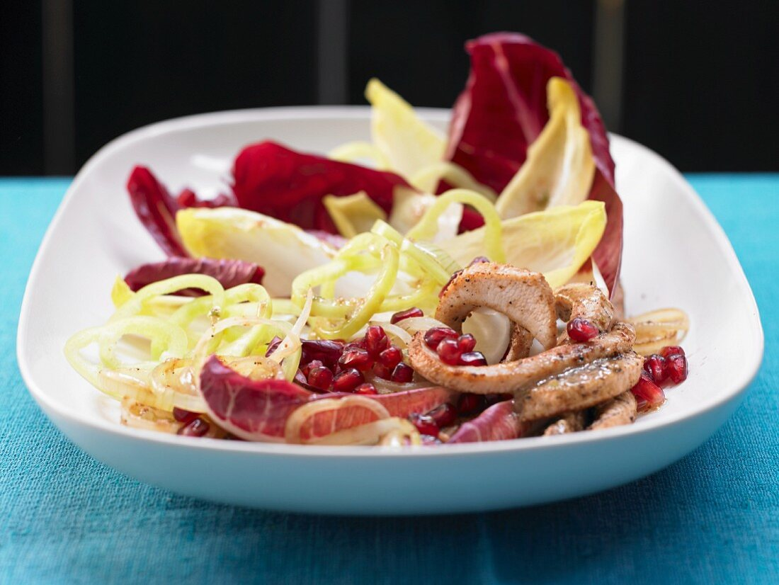A chicory salad with strips of turkey and pomegranate seeds