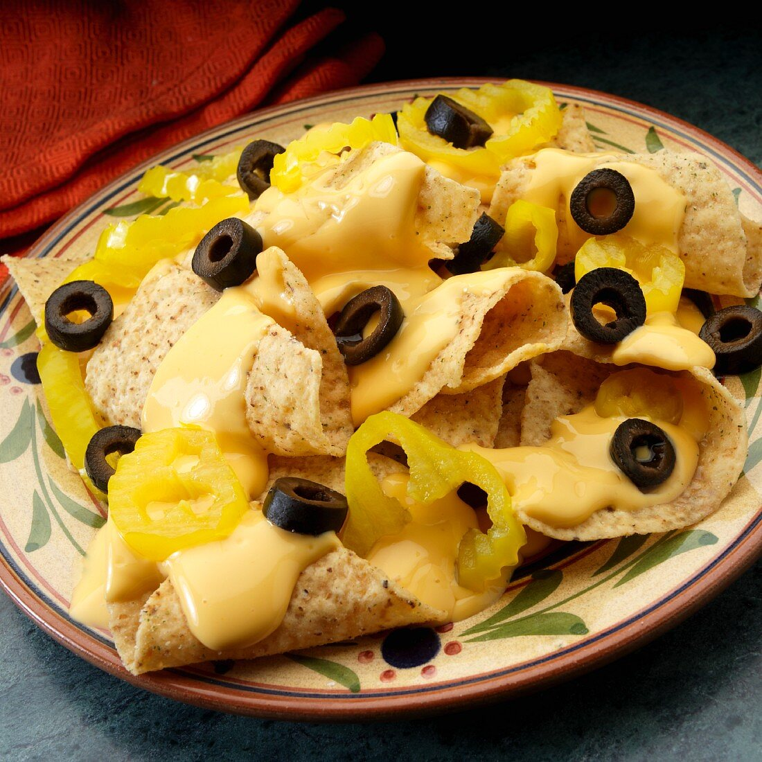 White corn tortilla chips with cheese sauce, black olives and banana peppers