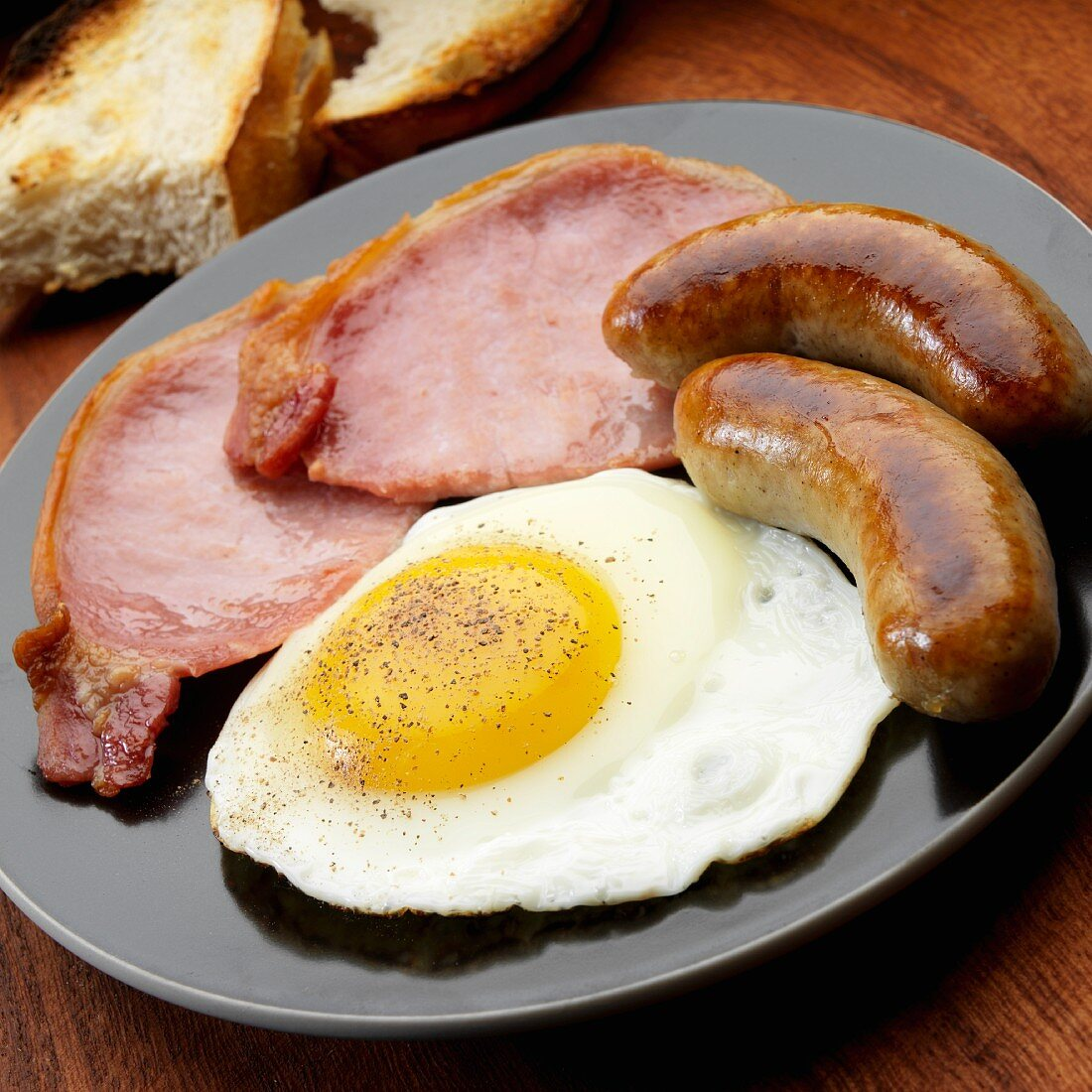 Fried egg with two bangers and two English bacon