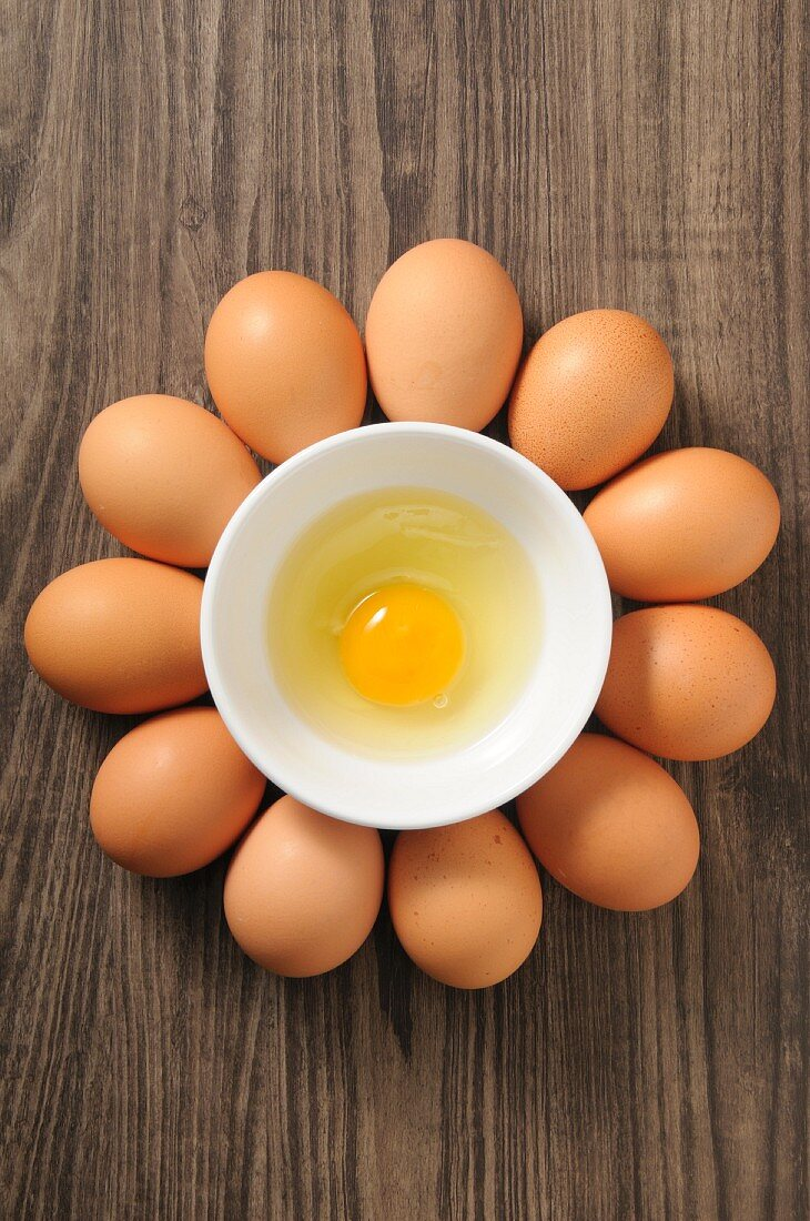 An egg yolk in a bowl surrounded by whole eggs