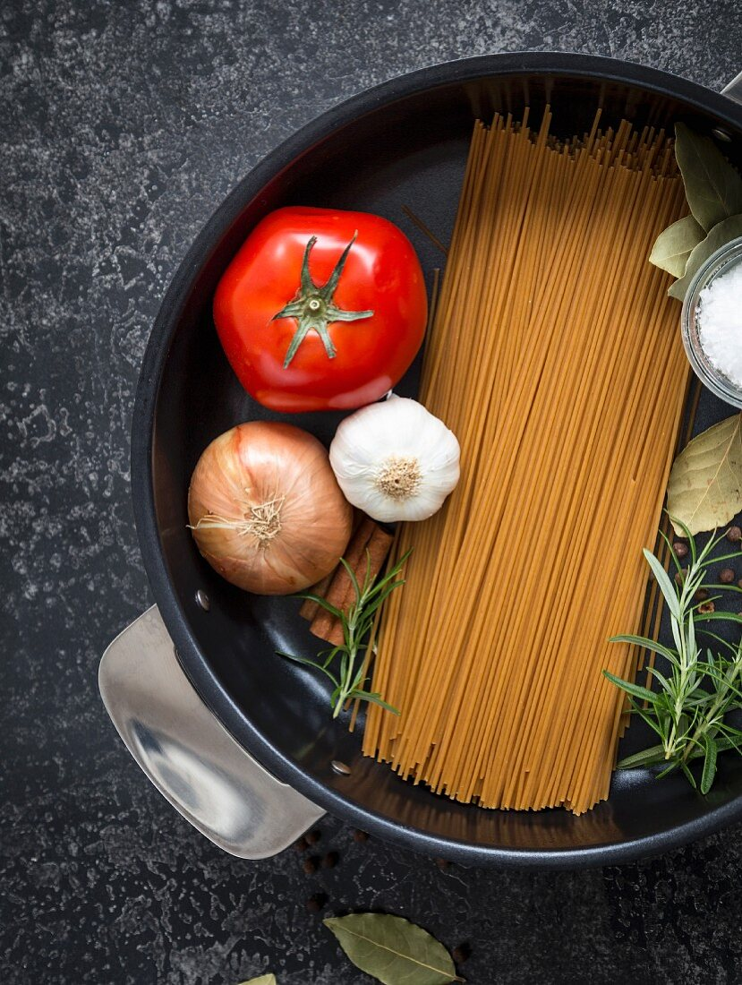 Ingredients for one-pot pasta: spaghetti, salt, tomatoes, rosemary, onion, tomatoes, bay leaves, a cinnamon stick and garlic