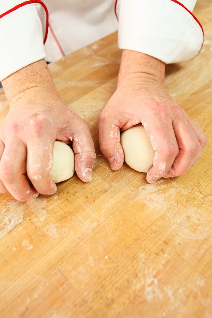 Dough being shaped into round balls
