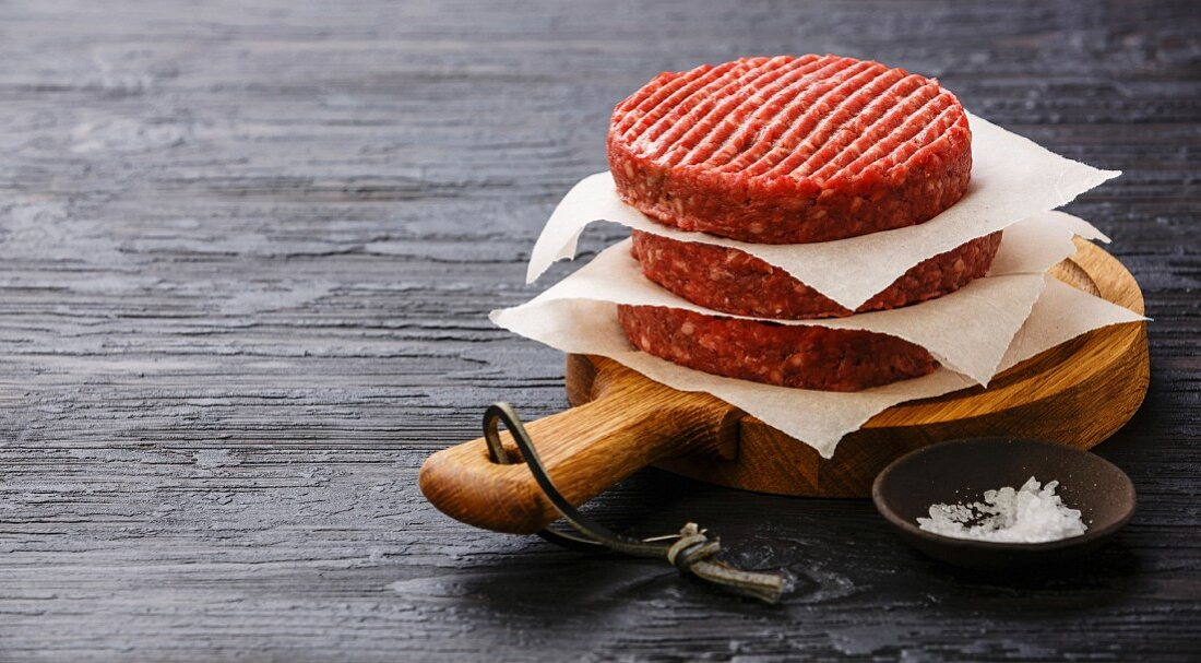Raw Ground beef meat Burger cutlets and on black burned wooden background copy space