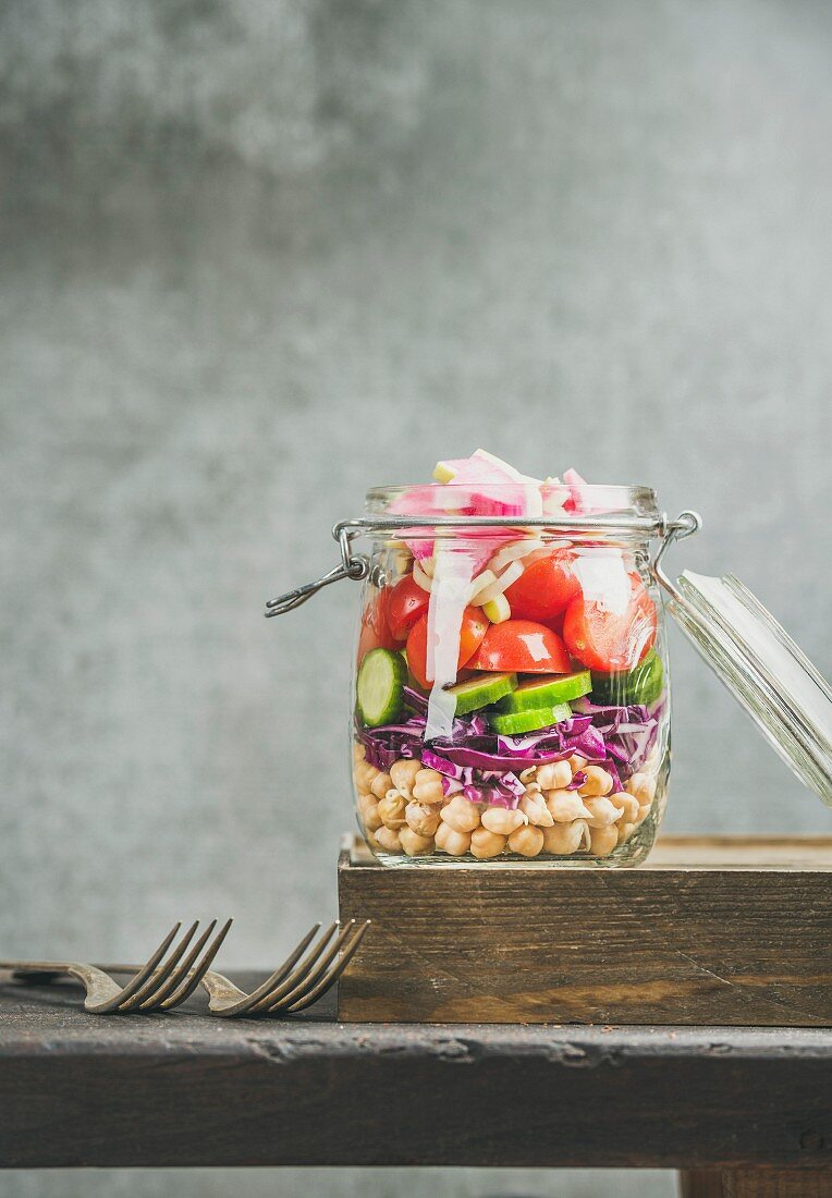Healthy take-away lunch jar. Vegetable and chickpea sprout layered vegan salad in glass jar