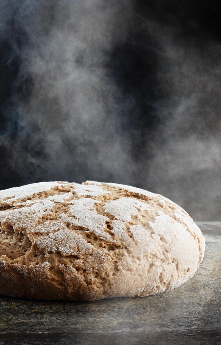 A steaming loaf of bread in the oven