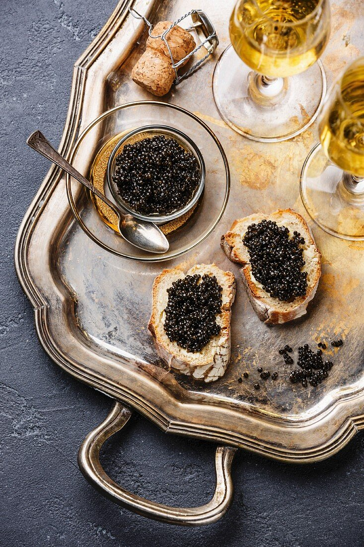 Sturgeon black caviar, sandwiches and champagne on silver tray