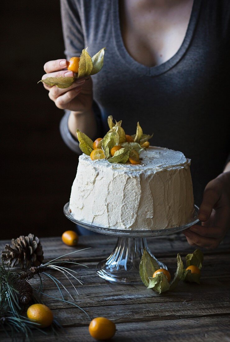Woman is decorating a chiffon cake on wooden table