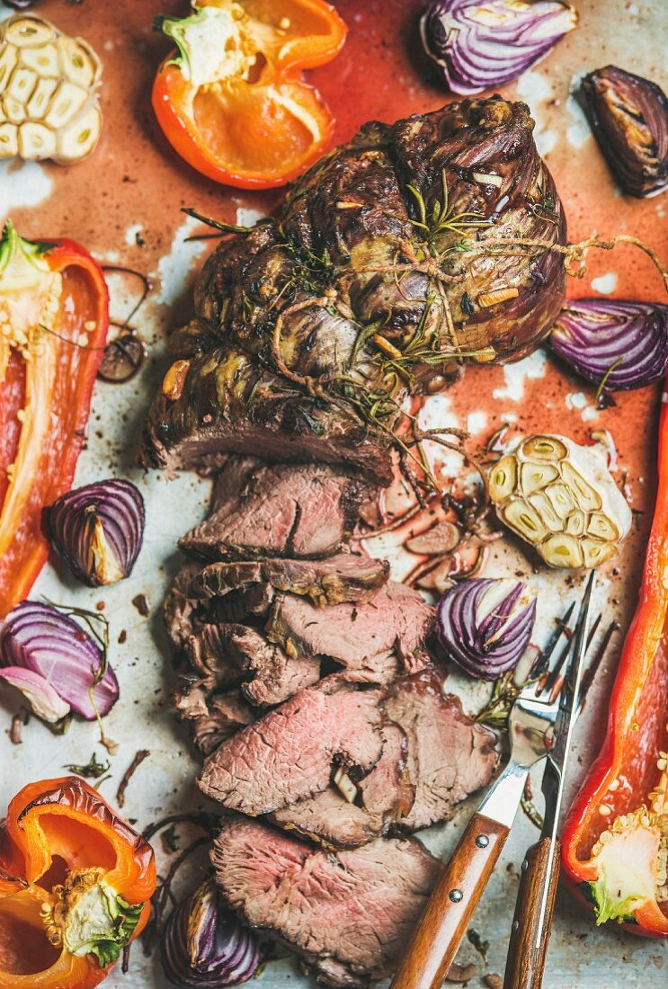 Cooked Roast beef meat with roasted vegetables and herbs in metal baking tray, top view