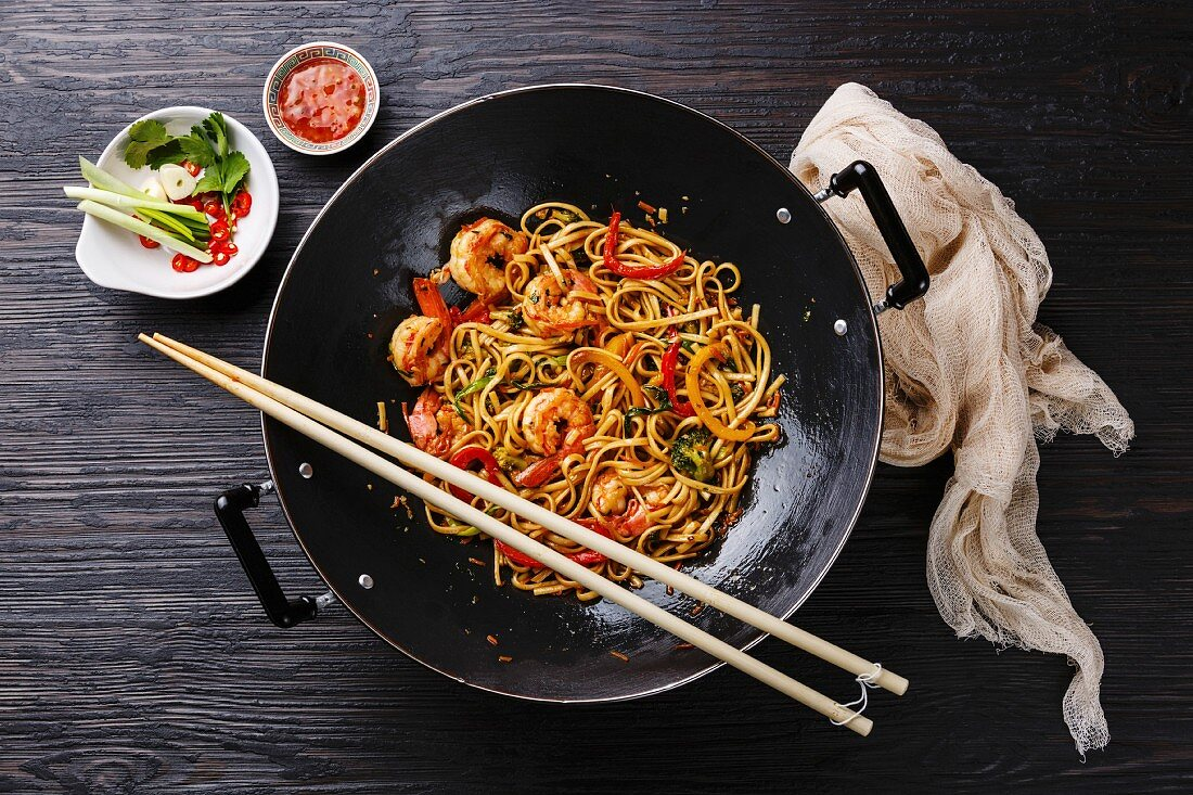 Udon stir-fry noodles with shrimp and vegetables in wok pan on black burned wooden background