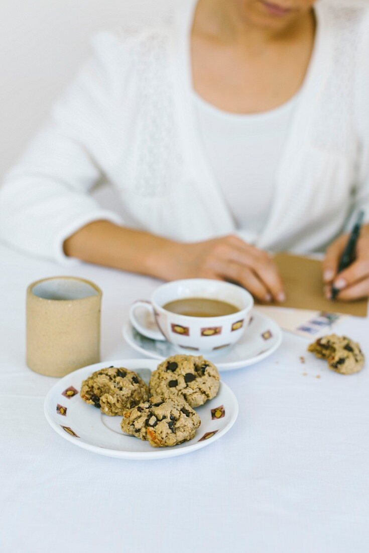 A woman writing a letter while having oatmal cookies and coffee