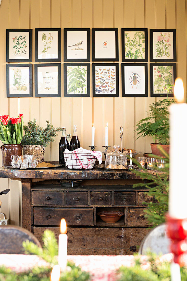 A Christmas buffet served on an old workbench with drawers, below a series of framed illustrations