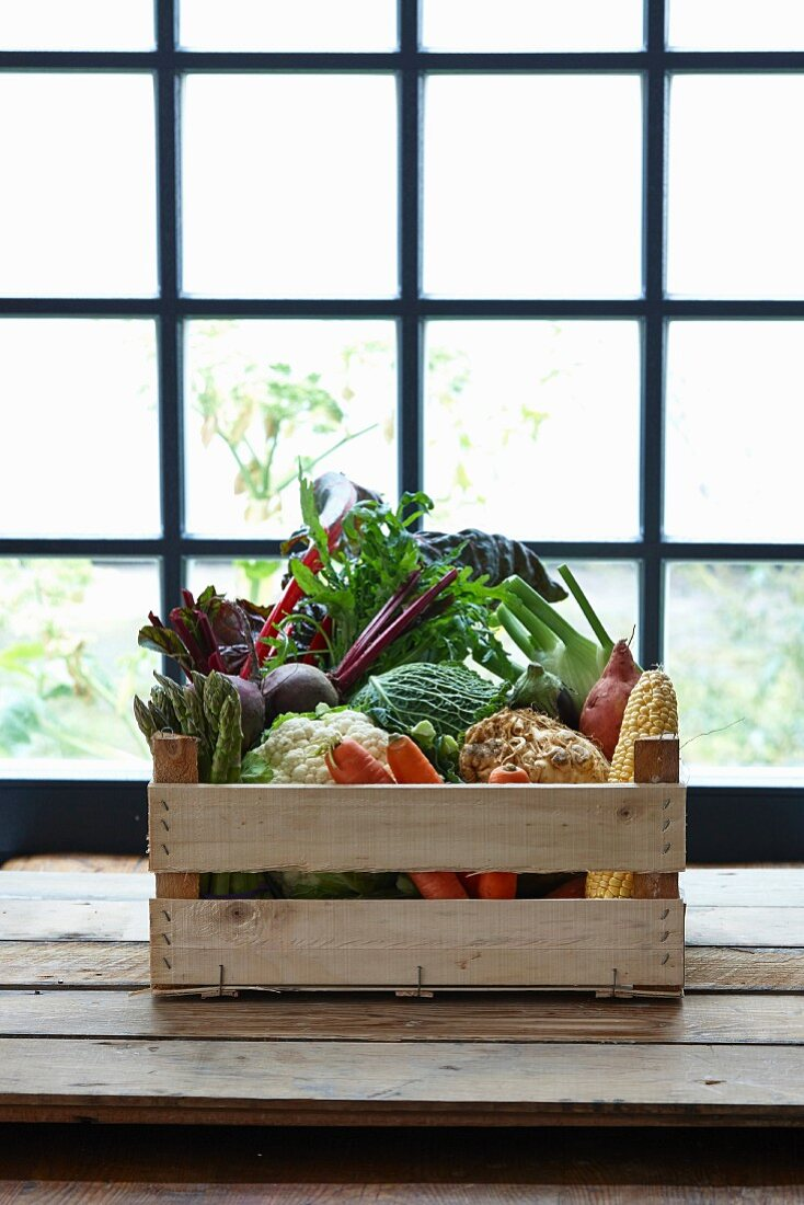 A crate of vegetables in front of a window